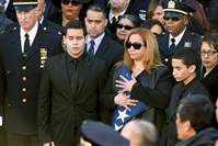 Maritza Ramos, wife of Office Rafael Ramos, holds the American flag as she is joined by her sons Justin, left, and Jaden, during Officer Ramos' funeral.