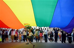 Elijah Socie, 6, of Brookline runs underneath a large pride banner to celebrate a federal judge ruling Pennsylvania's ban on same-sex marriage unconstitutional.