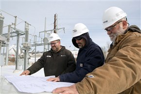 Substation electrician Chris Lyle, left, along with supervisor Jack Cole, center, and John Teyssier review the blueprints for future substation improvements at the Nyswaner Substation in Houston. The facility was built in 2011 to service a MarkWest gas processing plant.