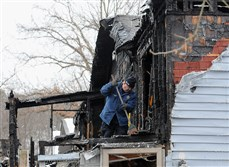 An Allegheny County Fire Marshall's investigator sifts through debris Sunday morning after a fatal fire.