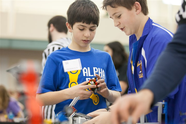 20150117rmlarocherobotics-3-1 Christian Farls, 12, and Matthew Soller, 13, students at Providence Heights Alpha School, prepare their robot before the Lego robotics competition at La Roche College in McCandless.