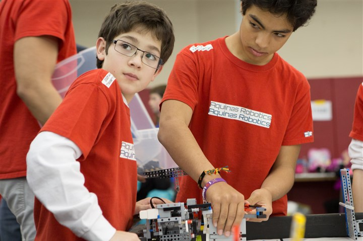 20150117rmlarocherobotics-3 Peter Alfaro, 11, left, and Alex Garcia, 13, students on the Aquinas Academy team, prepare their Lego robot for the competition Saturday at La Roche College in McCandless.