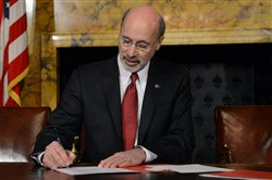 Gov. Tom Wolf signs two executive orders shortly after his swearing-in Tuesday.