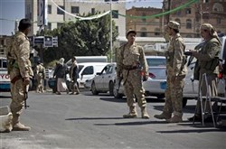 Houthi Shiite Yemeni wearing army uniforms stand guard on a street leading to the presidential palace in Sanaa, Yemen, today.