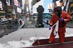 Francisco Mathurine, of the Times Square Alliance, clears snow from the steps in Father Duffy Square in New York, Monday, Jan. 26, when Broadway cancelled all shows due to the coming storm.