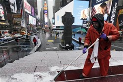 "Francisco Mathurine clears snow from the steps in Father Duffy Square in New York today. Officials cautioned Northeast residents to not be misled by a relatively smooth Monday morning commute, and pressed their cautions to prepare for a ""crippling and potentially historic"" storm."