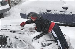 A young man works hard to clean off a car as snow continues to fall this morning. The National Weather Service said southwestern Pennsylvania could see another 1 to 2 inches of snow today.