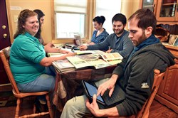 Justin Dillner looks at the computer while he and his family plan their planting and buying schedule for Dillner Family Farm at the kitchen table of their Gibsonia home. Seated around the table are, from left, Jane Dillner, Marie Dillner, intern Jenalee Schenk and Jon Dillner.