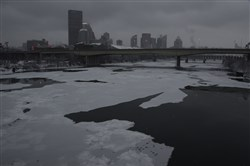 Snow highlights  a thin layer of ice on the Allegheny River , heading toward  the Pittsburgh skyline.