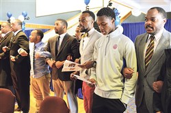 Mentors and students link arms as they recite their Manhood Statement at the beginning of the We Promise Scholars gathering Wednesday at Duquesne University.