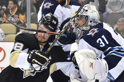 Penguins center Zach Sill takes a stick to the face by Winnipeg Jets defenseman Paul Postma during the first period at Consol Energy Center.
