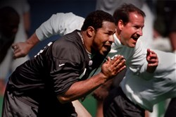 From the archives: Running back Jerome Bettis races with head coach Bill Cowher during a 1997 practice.