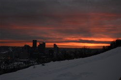 The Pittsburgh skyline rises against the red morning light with the snow laying near Grandview Avenue on Mount Washington.