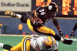 From the archives: Jerome Bettis, top, flies over Green Bay's LeRoy Butler for some of his 100 yards on the night Monday, Nov. 10, 1998, at Three Rivers Stadium. The Steelers beat the Packers 27-20.
