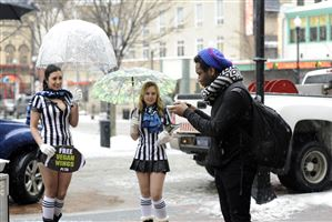 Topher Williams, a theater student at Point Park Unversity, approves of a vegan wing in Market Square. PETA volunteers Leila Sleiman of Pittsburgh and Ashley Bouvy of Mount Washington were handing out samples from a South Side restaurant, The Double Wide Grill.