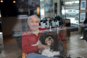 Luigi Caruso of Luigi Caruso Hair Care Studio watches the winter weather with his dog Bella, a Shih Tzu, Downtown.