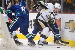 The Penguins' Sidney Crosby, right, moves the puck as the Canucks' Yannick Weber watches in the first period of their game Saturday night in Vancouver, British Columbia. The Canucks won the game, 5-0.