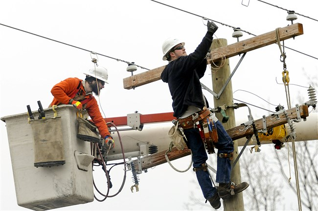 Mike Baranovich (left) and Clint Sarver, second-year students in an electric utility program, work atop a utility pole.