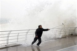 In this file photo, a man takes a selfie by a crashing wave on Beirut's Corniche, a seaside promenade, as high winds sweep through Lebanon during a storm.