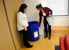 Kelly Porter, left, property manager of the Century Building, and Mary Kate Ranii, Pennsylvania Resources Council Program coordinator, set up a recycling bin in the Downtown apartment building.