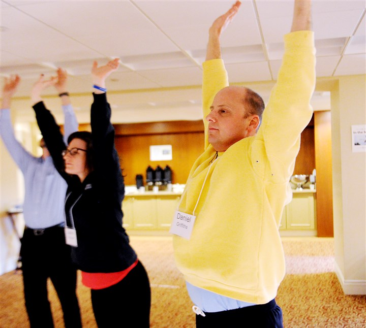 021315JHHealthMindlfulness03-1 Nurse Laura Schubert, left, and nurse Daniel Griffiths, right, do stretching exercises at mindfulness training for UPMC nurses.