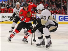 Chicago Blackhawks center Andrew Shaw (65) skates with the puck as  Penguins right winerg Steve Downie (23) defends in the first period at United Center in Chicago.