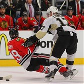 Chicago Blackhawks center Jonathan Toews is checked by Penguins left wing Blake Comeau during the second period yesterday at the United Center.