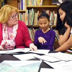 "20150213smsouthesl005-4 Renee Christman, teacher of English as a Second Language at Paynter Elementary School, chats with fourth-grade students Anisha Subba, center, and Subekshya Tamang on Feb. 13. ESL students at Paynter, part of Baldwin Whitehall School District, their refugee family members, and other refugee community members, are involved in a bilingual book project called ""Saving Stories"" to preserve folktales, biographical, and other types of information from their native cultures."