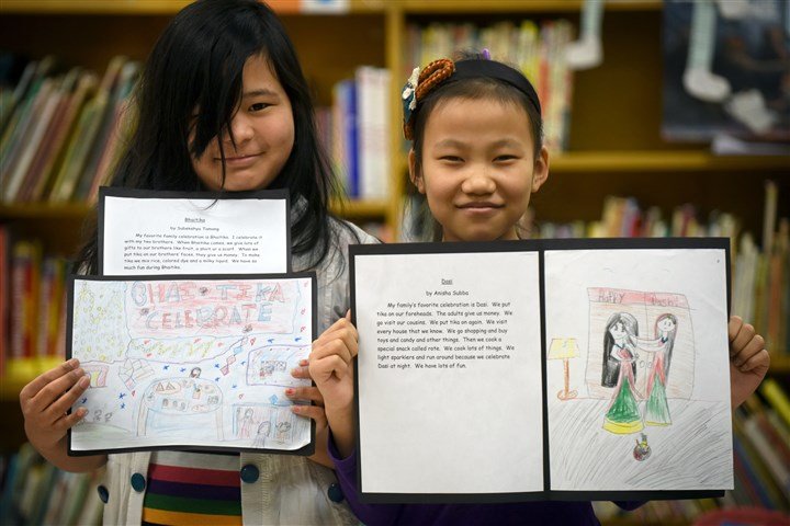 20150213smsouthesl001 Subekshya Tamang, left, and Anisha Subba, both fourth grade students at Panter Elementary School, display writings and illustrations about a favorite Nepali holiday.