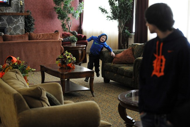 Jared Jones, 14, right, watches Wednesday as his brothers Cayden Carelli, 6, center, and Cruz Carelli, 4, run through the lobby of a hotel in Oak Hill, W.Va. The Carellis live in Adena Village and were evacuated after the train derailment, but are not allowed to return.