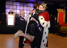 David Malone, this year's king, hugs Cindy Shapira as David Shapira watches. The Shapiras were last year's king and queen.