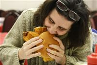 Ben Avon resident Beth Curran takes a bite out of her fish sandwich at St. Maximilian Kolbe Parish in Homestead.