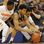 Pitt's Derrick Randall, center, and Syracuse's Kaleb Joseph, left, and Michael Gbinije dive for a loose ball in the first half.