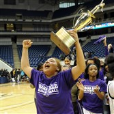 Obama Academy's Bre Clifford holds the trophy after defeating Allderdice Saturday afternoon in the City League championship at the Petersen Events Center.