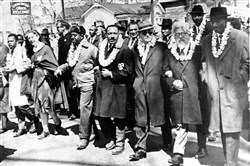 The Rev. Martin Luther King Jr., fourth from right, links arms with other civil rights leaders as they begin the march to the state capitol in Montgomery from Selma, Ala., on March 21, 1965. The demonstrators are marching for voter registration rights for black residents. Second from right is Rabbi Abraham Joshua Heschel. The marchers are wearing leis given by a Hawaiian group.