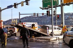 A crew works to remove the crashed white Denali from the Fort Pitt Boulevard and Wood Street intersection on Feb. 25.