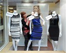 Shop manager Debbie Armstrong adjusts the two-tone dress Friday in a window display of a shop in Lichfield, England.