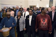"Community members and Pittsburgh Police Chief Cameron McLay, back center, hold hands Thursday before the blessing of the offering and closing prayer during ""Moving from Marches to Measurables,""  a community meeting hosted by Pennsylvania Interfatih Impact Network at Baptist Temple Church in Homewood."