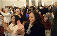 The Rev. Jacqueline Lyde of Shadyside and others cheer during a community meeting with Pittsburgh police Chief Cameron McLay at Baptist Temple Church in Homewood.