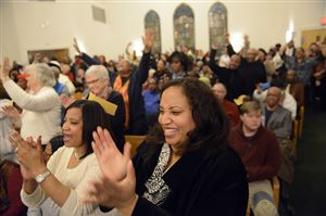 Rev. Jacqueline Lyde of Shadyside and others cheer during a community meeting hosted by Pittsburgh Interfaith Impact Network community members and Pittsburgh police Chief Cameron McLay at Baptist Temple Church in Homewood on Thursday.