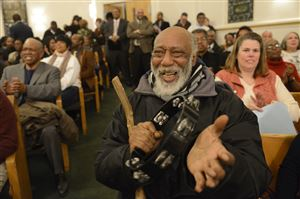 "Al Johnson of Penn Hills makes some noise in support of speakers during ""Moving from Marches to Measurables,"" a community meeting hosted by Pittsburgh Interfaith Impact Network for community members and Pittsburgh police Chief Cameron McLay at Baptist Temple Church in Homewood."