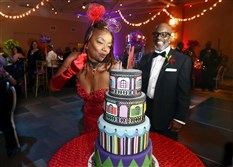 "Katie ""Peachie"" Wimbush-Polk, mother of Wiz Khalifa, blows out birthday cake candles, as her husband Richard Polk watches."