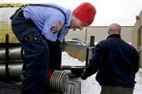 The Club Sport and Health in Monroeville is donating fitness equipment and weights to the Monroeville Volunteer Fire Company No. 1. Here, Jason Darnley tries to lift a weight into the bed of a truck.