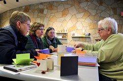 From left, Linda Patory of Penn Hills, Jackie Mignogna of North Huntingdon and Karen Yount of Plum learn how to make a book from Pat Buckley of Bloomfield.
