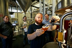Wayne Carpenter, left, Bob Rock of the Skagit Valley Malting Company and Emerson Lamb, co-founder of Westland Distillery, watch as Matt Hofmann, master distiller at Westland Distillery, draws the first sample of a wort made from barley grown in the Skagit Valley.
