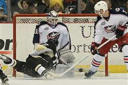 Patric Hornqvist dives into the net as the puck gets by Blue Jackets goaltender Curtis McElhinney on a shot by Evgeni Malkin for a power play goal in the second period Sunday, March 1, 2015, at the Consol Energy Center.