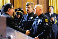 Pittsburgh Mayor Bill Peduto congratulates Lt. William Blair during a Pittsburgh Bureau of Police promotion ceremony held in the City Council Chambers in the City-County Building on Tuesday.