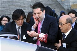 Injured U.S. Ambassador to South Korea Mark Lippert, center, gets into a car to leave for a hospital in Seoul, South Korea, today after he was attacked by a man wielding a razor and screaming that the rival Koreas should be unified, South Korean police said.