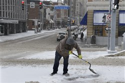 Jim Cyprych of Hazelwood clears snow off a crosswalk on Fort Pitt Boulevard near the Smithfield Street intersection.