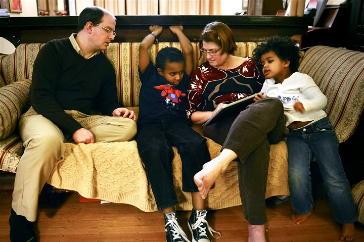 The Pattersons Kevin and Ali Patterson, along with their daughter Didi, 4, at right, look at photos of their son Robert, 8, during his early childhood in Ethiopia at their home Tuesday in Point Breeze.